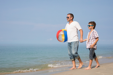 Father and son playing on the beach at the day time. People having fun outdoors.  Concept of happy vacation and friendly family. Standard-Bild - 116775772