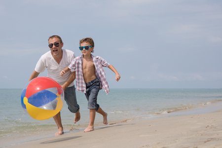 Father and son playing on the beach at the day time. People having fun outdoors.  Concept of happy vacation and friendly family. Standard-Bild - 116775785