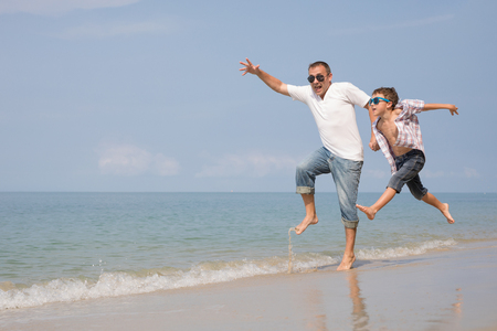 Father and son playing on the beach at the day time. People having fun outdoors.  Concept of happy vacation and friendly family. Standard-Bild - 116775908