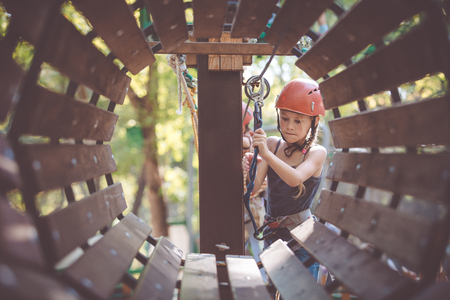 little brother and sister make climbing in the adventure park at the day time. Concept of happy game. Child having fun outdoors. Standard-Bild - 116775909