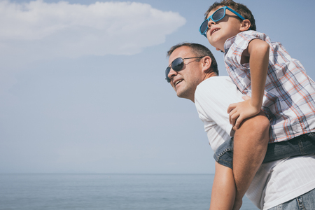 Father and son playing on the beach at the day time. People having fun outdoors.  Concept of happy vacation and friendly family. Standard-Bild - 116777618