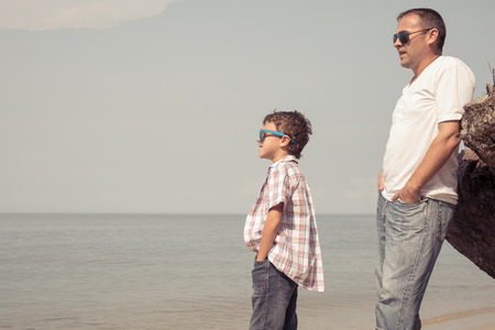 Father and son playing on the beach at the day time. People having fun outdoors.  Concept of happy vacation and friendly family. Standard-Bild - 116777653