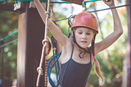 little brother and sister make climbing in the adventure park at the day time. Concept of happy game. Child having fun outdoors. Standard-Bild - 116777656