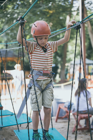 little boy make climbing in the adventure park. Concept of sport life. Standard-Bild - 116777664