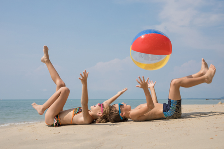 Two happy little children playing on the beach at the day time.  Kids having fun outdoors. Concept of kids on vacation and friendly family. Standard-Bild - 116777667