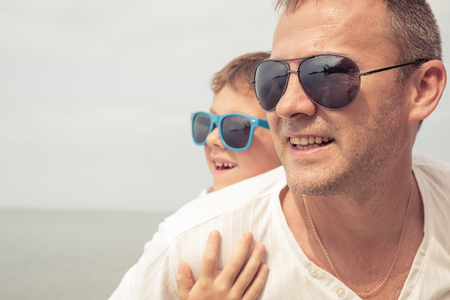 Father and son playing on the beach at the day time. People having fun outdoors.  Concept of happy vacation and friendly family. Standard-Bild - 116777678