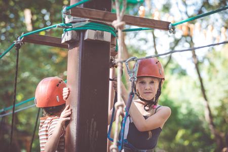 little brother and sister make climbing in the adventure park at the day time. Concept of happy game. Child having fun outdoors. Standard-Bild - 116777682