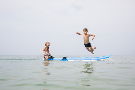Happy children playing on the beach at the day time. Two Kids having fun outdoors. Concept of summer vacation and friendly family. Standard-Bild - 116777784