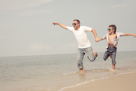 Father and son playing on the beach at the day time. People having fun outdoors.  Concept of happy vacation and friendly family. Standard-Bild - 116777785
