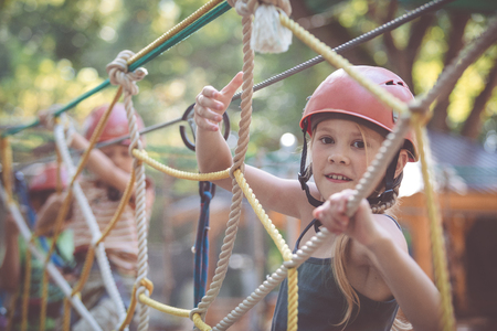 little brother and sister make climbing in the adventure park at the day time. Concept of happy game. Child having fun outdoors. Standard-Bild - 116777792