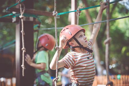 little boy make climbing in the adventure park. Concept of sport life. Standard-Bild - 116777822