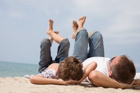 Father and son playing on the beach at the day time. People having fun outdoors.  Concept of happy vacation and friendly family. Standard-Bild - 116777831