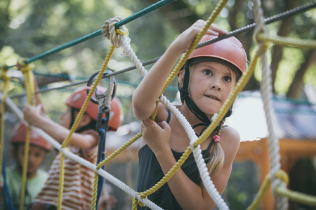 little brother and sister make climbing in the adventure park at the day time. Concept of happy game. Child having fun outdoors. Standard-Bild - 116777836