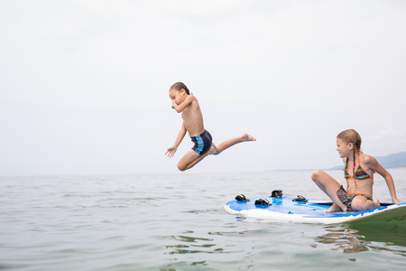Happy children playing on the beach at the day time. Two Kids having fun outdoors. Concept of summer vacation and friendly family. Standard-Bild - 116777842