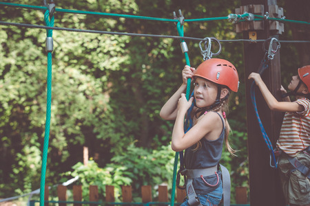 little brother and sister make climbing in the adventure park at the day time. Concept of happy game. Child having fun outdoors. Standard-Bild - 116777845