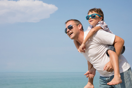 Father and son playing on the beach at the day time. People having fun outdoors.  Concept of happy vacation and friendly family. Standard-Bild - 116777847