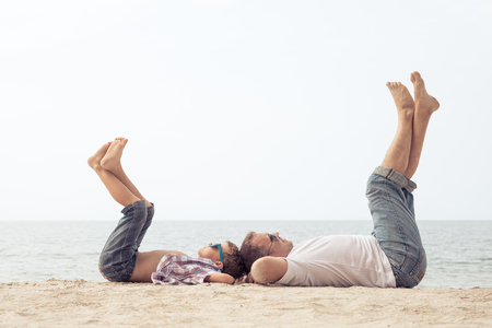 Father and son playing on the beach at the day time. People having fun outdoors.  Concept of happy vacation and friendly family. Standard-Bild - 116780826