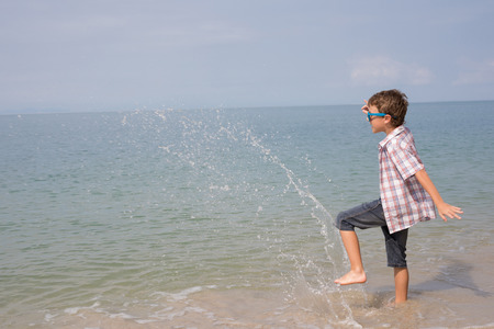 One happy little boy playing on the beach at the day time. Kid having fun outdoors. Concept of vacation. Standard-Bild - 116780835
