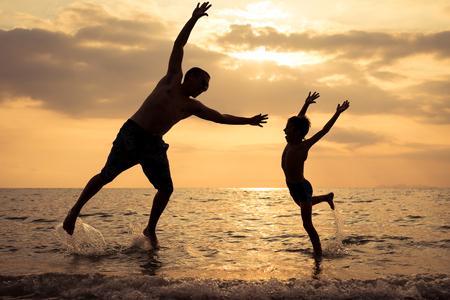 Padre e hijo jugando en la playa al atardecer. Gente divirtiéndose al aire libre. Concepto de felices vacaciones y familia amistosa.