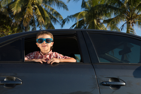 One happy little boy sitting in the car at the day time. Concept of summer vacation.