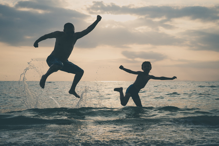 Father and son playing on the beach at the sunset time. People having fun outdoors.  Concept of happy vacation and friendly family. 写真素材 - 122395193