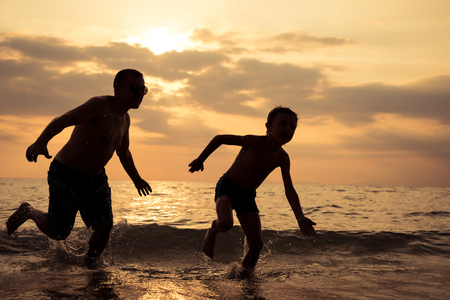 일몰 시간에 해변에서 노는 아버지와 아들. 야외에서 즐거운 시간을 보내는 사람들. 행복한 휴가와 친절한 가족의 개념.