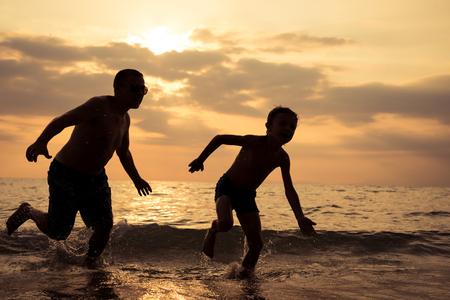 Vader en zoon spelen op het strand bij zonsondergang. Mensen die buiten plezier hebben. Concept van gelukkige vakantie en vriendelijke familie.
