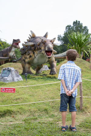 little boy playing in the adventure dino park. Concept of happy childhood. Stock Photo