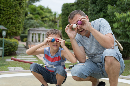 Happy father and little son playing mini golf in a park at the day time. People having fun otdoors. Concept of good leisure.