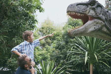 Happy father and son playing in the adventure dino park at the day time. People having fun outdoors. Concept of summer vacation and friendly family.