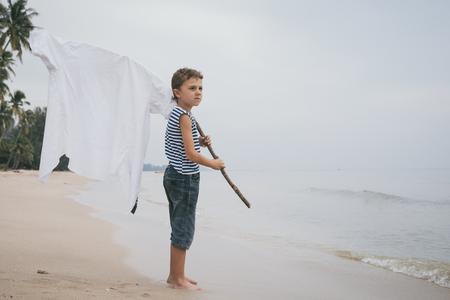 Un ragazzino che gioca sulla spiaggia durante il giorno. Bambino che gioca all'aperto. Concetto di vacanza estiva.