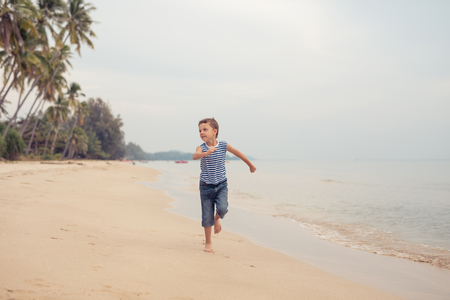 One happy little boy playing on the beach at the day time.  Kid having fun outdoors. Concept of summer vacation. Stock Photo