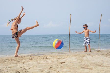 Due piccoli bambini felici che giocano sulla spiaggia durante il giorno. I bambini si divertono all'aperto. Concetto di bambini in vacanza e famiglia amichevole.