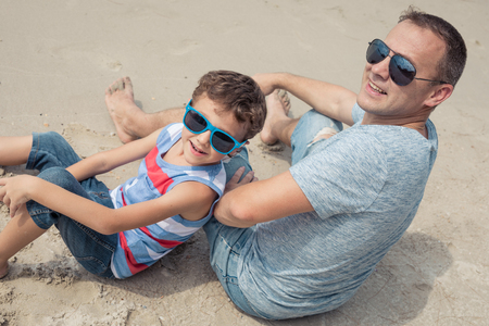 Father and son playing on the beach at the day time. People having fun outdoors. Concept of happy vacation and friendly family.