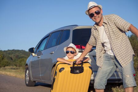 Happy father and son standing near the car at the day time. They look out the window. People having fun outdoors. Concept of the family is ready for travel.