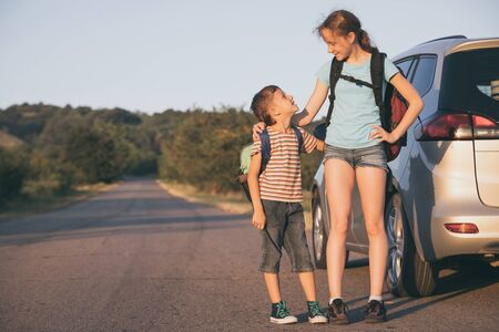 Happy brother and his  sister are standing near the car at the day time. Children having fun outdoors. Concept of the family is ready for travel.