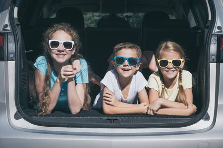 Happy brother and his two sisters are sitting in the car at the day time. Children having fun outdoors. Concept of the family is ready for travel.