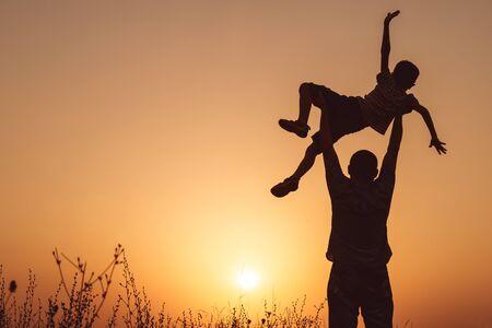 Vader en zoon spelen in het park op het moment van de zonsondergang. Mensen hebben plezier op het veld. Concept van vriendelijke familie en zomervakantie.