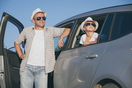 Happy father and son sitting in the car at the day time. They look out the window. People having fun outdoors. Concept of the family is ready for travel. Stock Photo