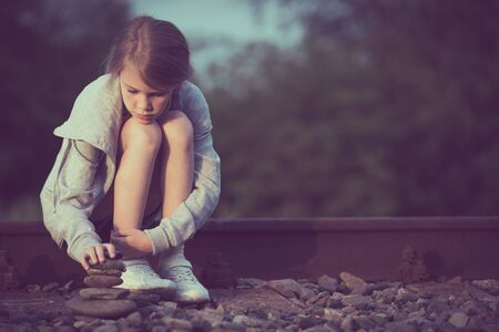 Portrait of young sad girl sitting outdoors  on the railway at the day time. Concept of sorrow.