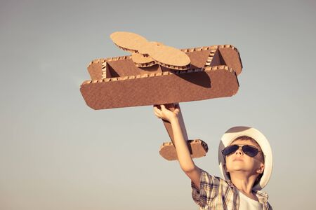 Little boy playing with cardboard toy airplane in the park at the day time. Concept of happy game. Child having fun outdoors. Picture made on the background of blue sky. Stockfoto