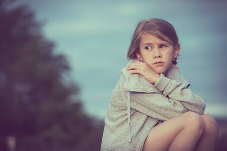 Portrait of young sad girl sitting outdoors on the railway at the day time. Concept of sorrow. Foto de archivo