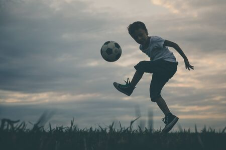 Young little boy playing in the field  with soccer ball. Concept of sport.