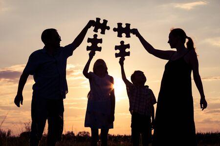 Glückliche Familie, die bei Sonnenuntergang im Park steht. Leute, die Spaß im Freien haben. Konzept der freundlichen Familie.