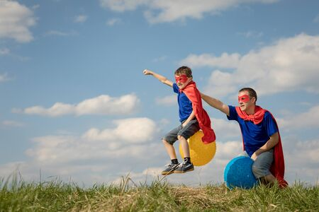 Father and son playing superhero at the day time. People having fun outdoors.They jumping on inflatable balls on the lawn. Concept of friendly family. Stockfoto