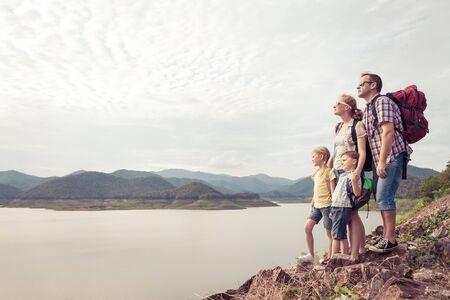 昼間に湖の近くに立っている幸せな家族。フレンドリーな家族の概念。