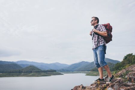 Happy man standing near the lake at the day time. Concept of success.