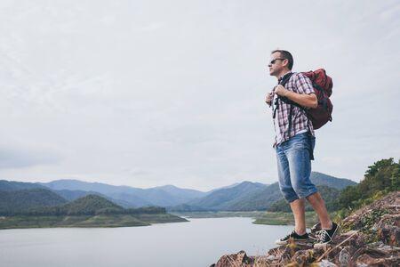 Heureux homme debout près du lac pendant la journée. Notion de succès.