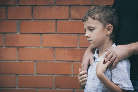 Portrait of young sad little boy and father standing outdoors at the day time. Concept of sorrow.