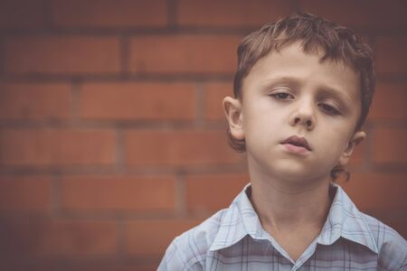 portrait one sad little boy standing near a wall  at the day time. Concept of sorrow. Stockfoto